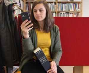 Kvinna anmäler via mobilen och har lagbok i knät