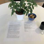 Brevet på vitt bord bredvid blomma och fika