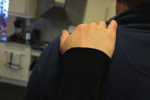 En hand vilar på en axel i ett kök. Illustration på en situation när någon stödjer en annan till exempel i ett gruppboende.