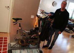 Urban Fernquist bredvid sin motionscykel hemma hos honom.