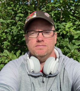 Mats Larsson, Sven Aiverts IT-support och nära vän. Selfie tagen framför grönska.