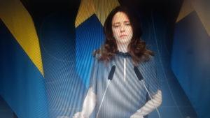Jämställdhetsminister Åsa Lindhagen framför en svensk flagga på en presskonferens.