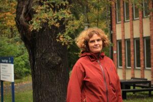 Jenny Rosendahl utanför specialpedagogiken, Stockhols universitet. Träd medhöstfärger i bakgrunden.