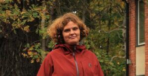 Närbild på Jenny Rosendahl utanför universitet med höst-grönska i bakgrunden.
