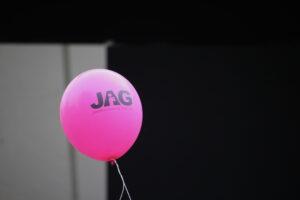 En rosa JAG-ballong mot svartgrå bakgrund.