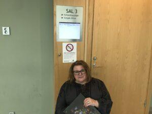 Maria Johansson vid förhandlingsskärm utanför rättssal.